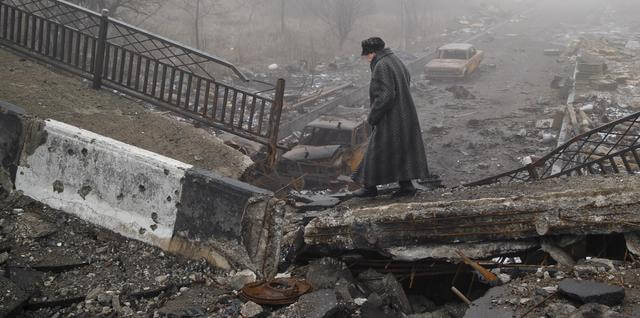 An elderly woman walks across a destroyed bridge, fallen onto the road towards the airport, the scene of heavy fighting in Donetsk, Ukraine, Sunday, March 1, 2015.  The recent pullback of some weapons from the line separating government and rebel forces in Ukraine seems to have boosted the prospects for peace, although both sides are warning of their readiness to resume fighting if necessary. (ANSA/AP Photo/Vadim Ghirda)